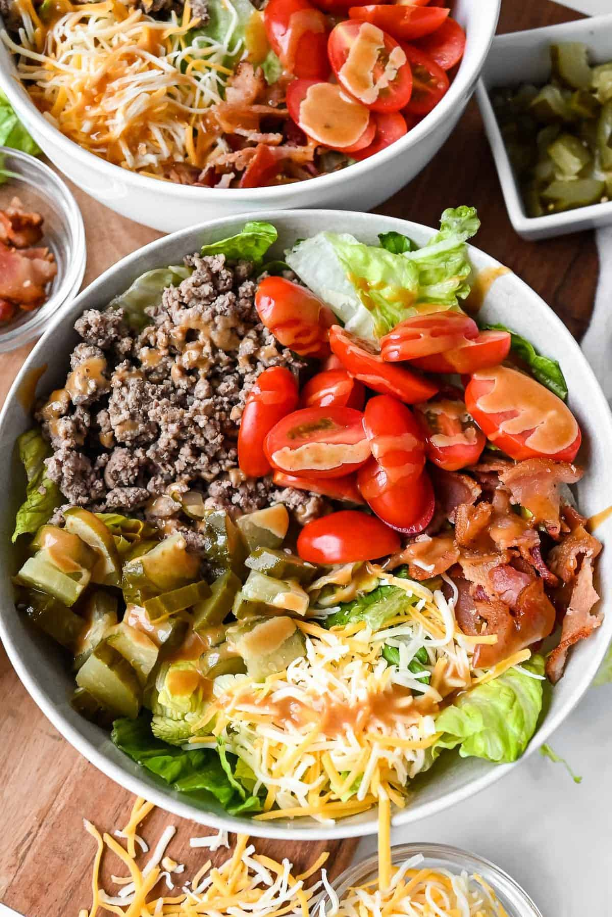 burger in a bowl with lettuce, bacon, tomatoes, cheese and special sauce
