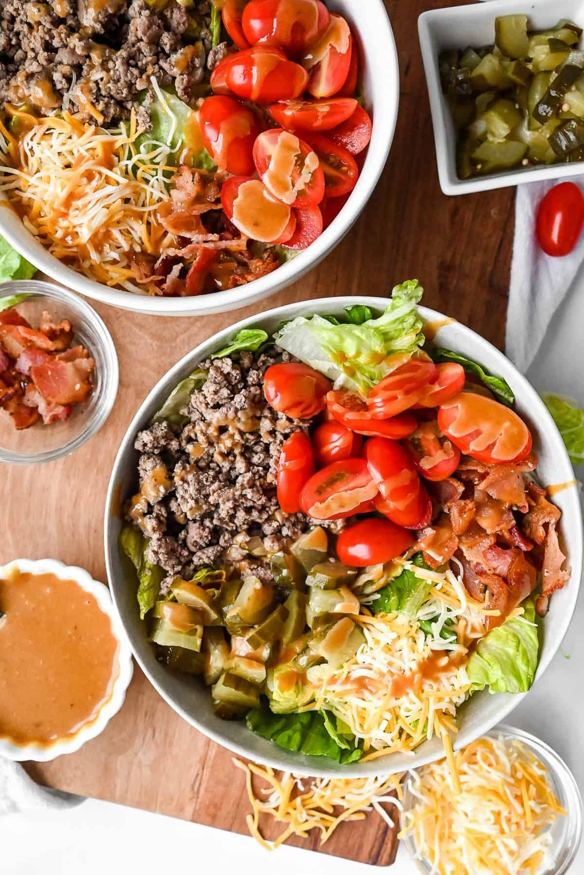two burger bowls on a tray with special sauce for burgers