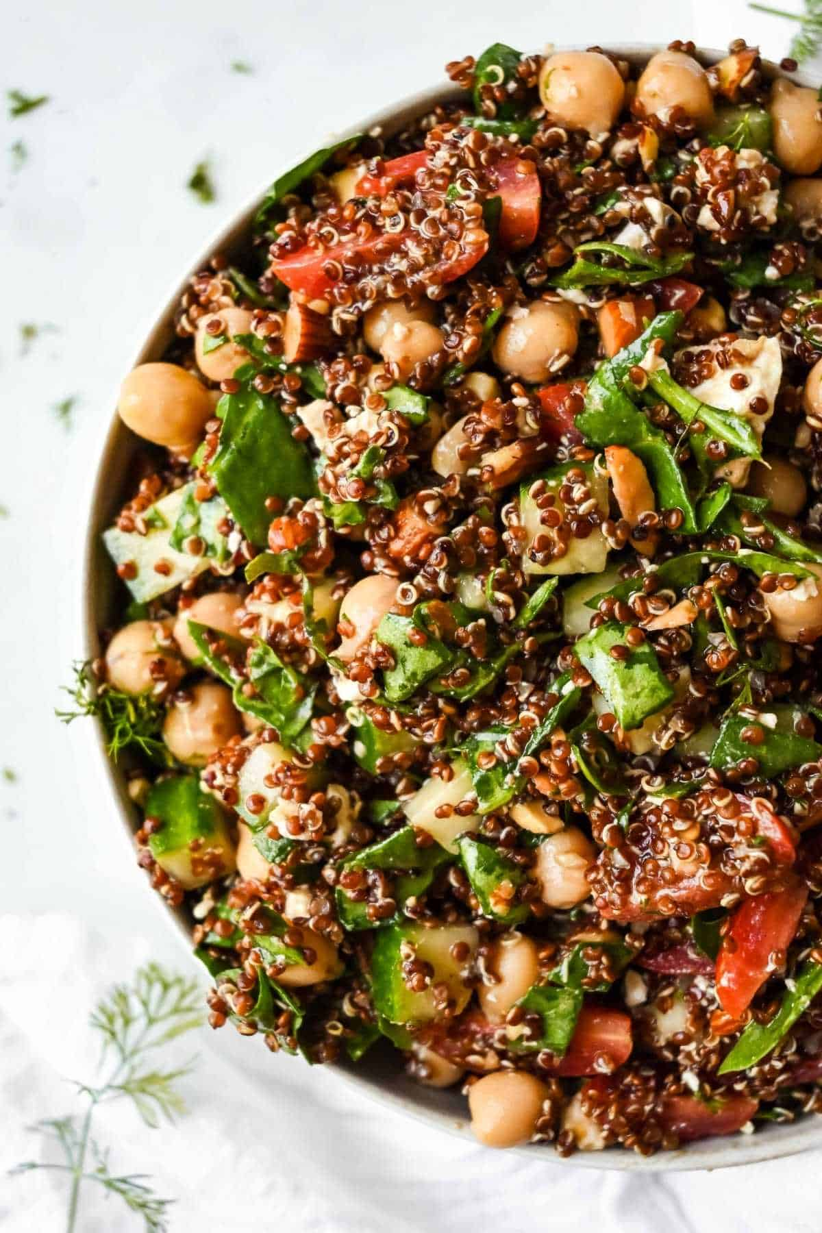 spinach quinoa salad in a bowl with fresh herbs