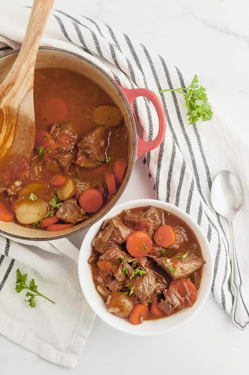 bowl of beef stew next to beef stew in a dutch oven