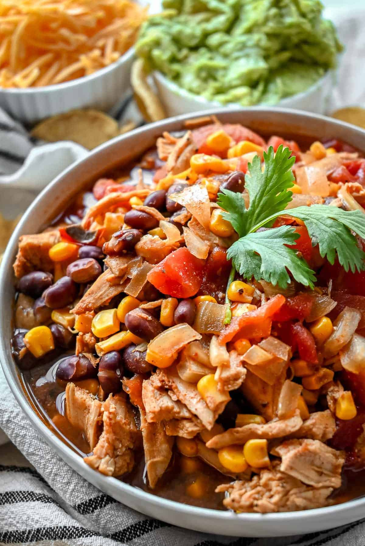 bowl of slow cooker enchilada soup with beans corn chicken and cilantro