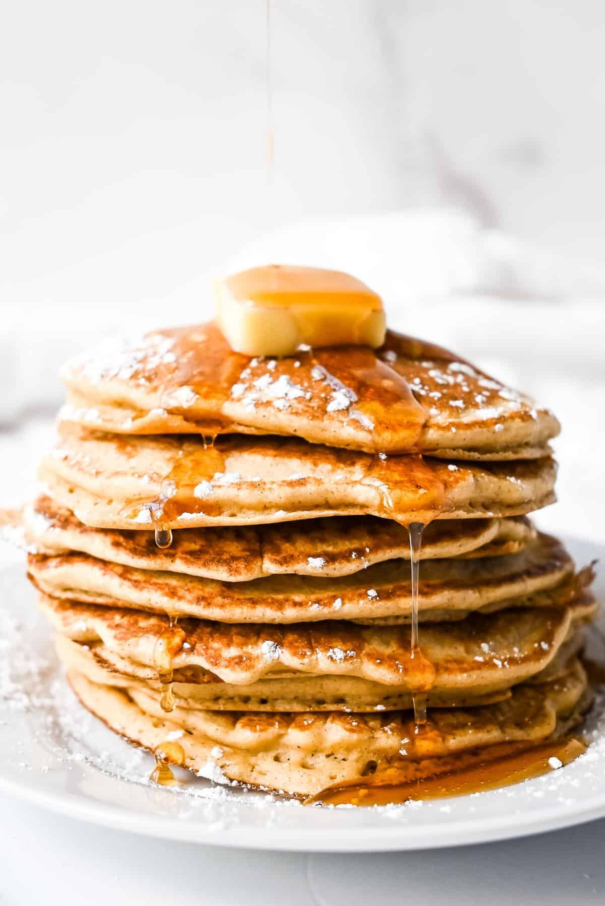 stack of oat flour pancakes with maple syrup, butter and powdered sugar