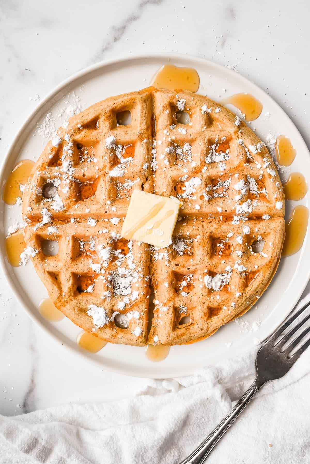 oat flour waffle on a plate topped with butter, maple syrup and powdered sugar