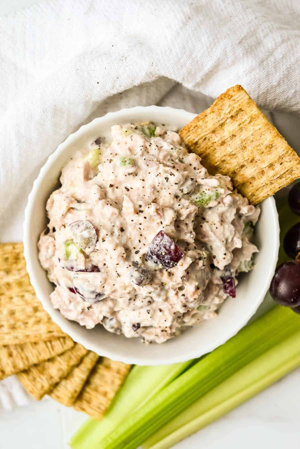 bowl of tuna salad with greek yogurt with crackers in a white bowl.