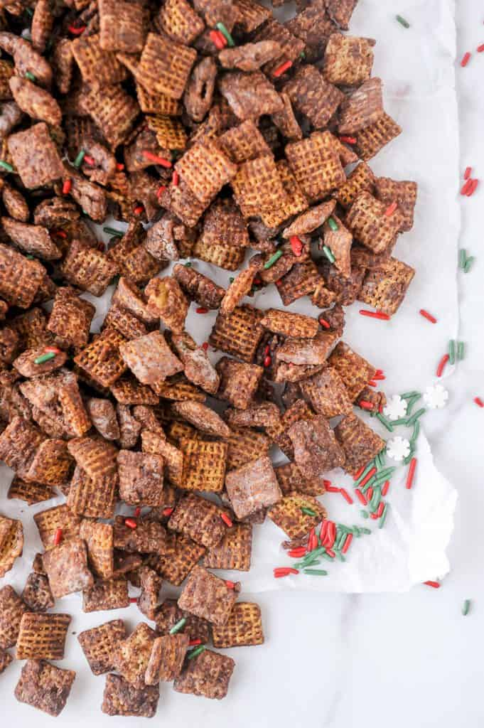 ingredients for skinny puppy chow on parchment paper with holiday sprinkles