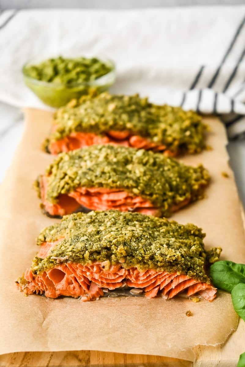 baked pesto crusted salmon filet on a board