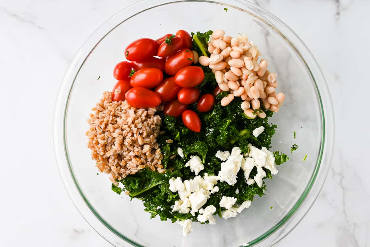 ingredients in a bowl for kale tomato salad
