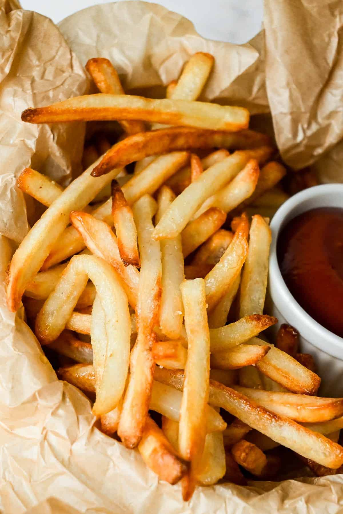 air fryer frozen french fries in a basket with ketchup