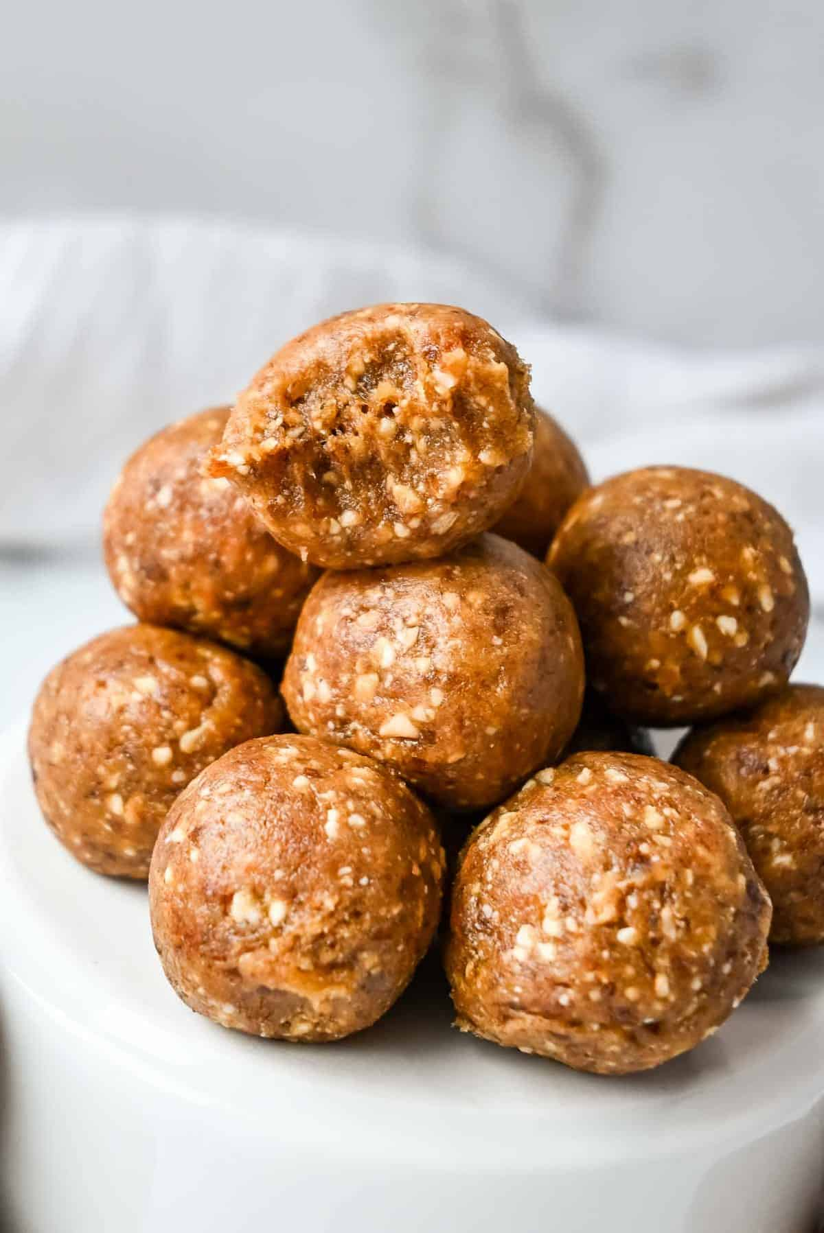 energy balls with dates in a stack with a bite taken out of the top one to show texture