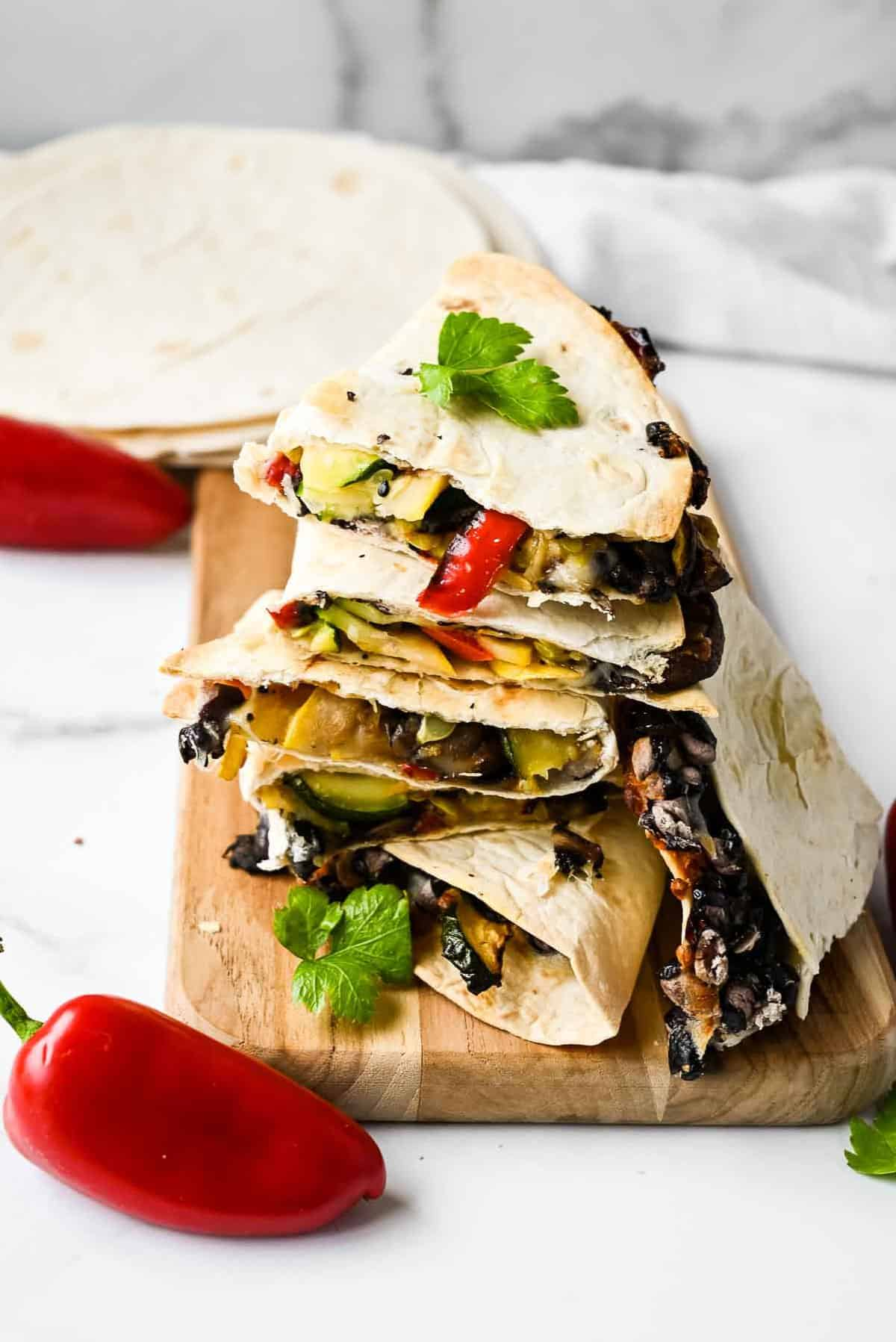 healthy quesadillas with beans in a stack with tortillas and peppers